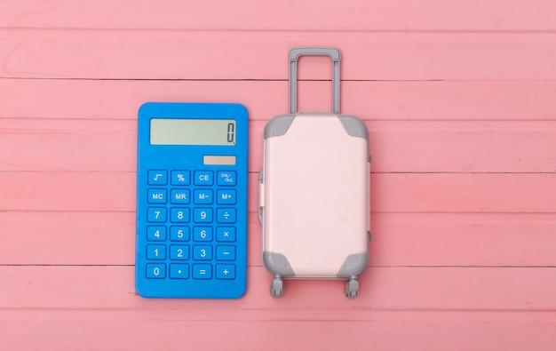 평평한 휴가 휴가 및 여행 계획 개념. 분홍색 나무 바탕에 미니 플라스틱 여행 가방과 계산기. 평면도