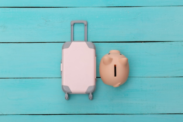 평평한 휴가 휴가 및 여행 계획 개념. 푸른 나무 배경에 미니 플라스틱 여행 가방과 돼지 저금통. 평면도