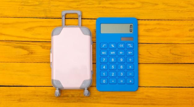 평평한 휴가 휴가 및 여행 계획 개념. 미니 플라스틱 여행 가방, 노란색 나무 바탕에 계산기. 평면도