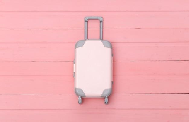 평평한 휴가 휴가 및 여행 계획 개념. 분홍색 나무 배경에 미니 플라스틱 여행 가방. 평면도