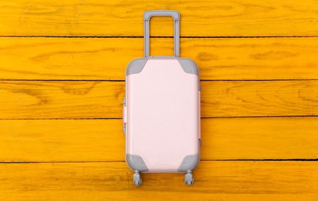 평평한 휴가 휴가 및 여행 계획 개념. 노란색 나무 바탕에 미니 플라스틱 여행 가방. 평면도