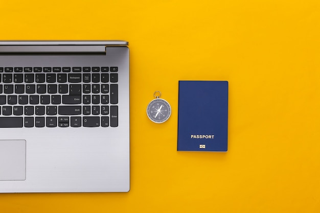 Flat lay vacation holiday and travel planing concept. laptop and passport, compass on yellow background. top view