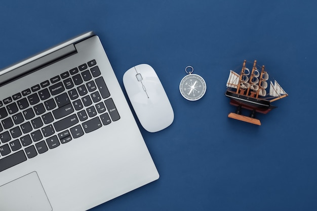 Flat lay vacation holiday and travel planing concept. laptop and travel accessories on classic blue background. top view