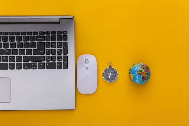 Flat lay vacation holiday and travel planing concept. laptop and travel accessories on yellow background. top view