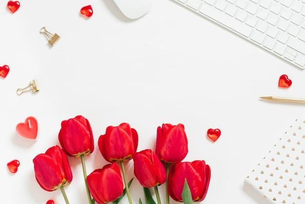 Плоский фон на день святого валентина с компьютерной клавиатурой, подарком, кофейной кружкой и красным тюльпаном, вид сверху, белая копия пространства