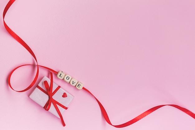 パステルピンクの壁の赤いリボンにフラットレイバレンタインデーのコンセプトワード愛。