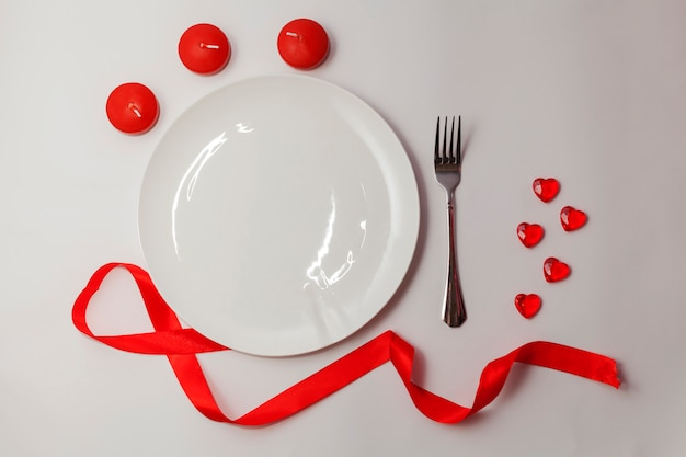 Flat lay valentines day. empty white plate on the table with red summer, hearts and candles and fork.