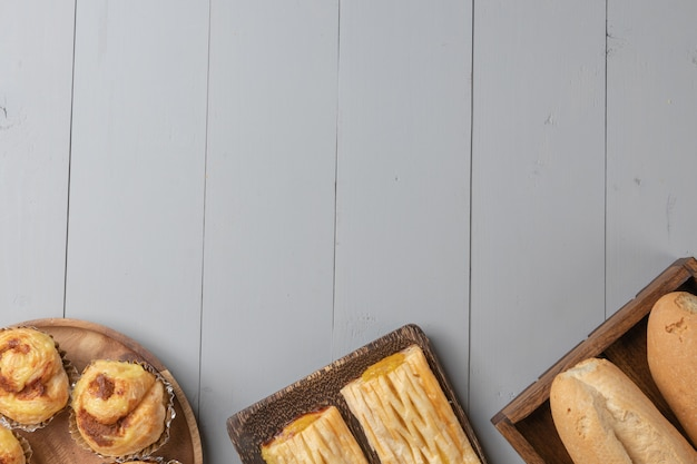 Flat lay of variety of bakery and pineapple pine on wooden board