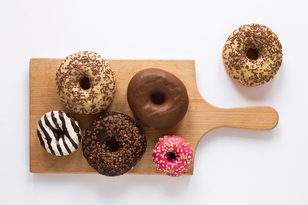 Flat lay of variety of donuts on chopping board