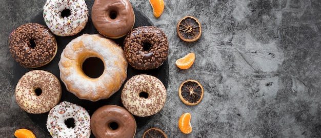 Flat lay of variety of doughnuts with dried citrus and copy space