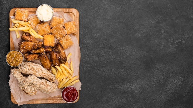 Flat lay of variety of fried chicken with sauces and copy space