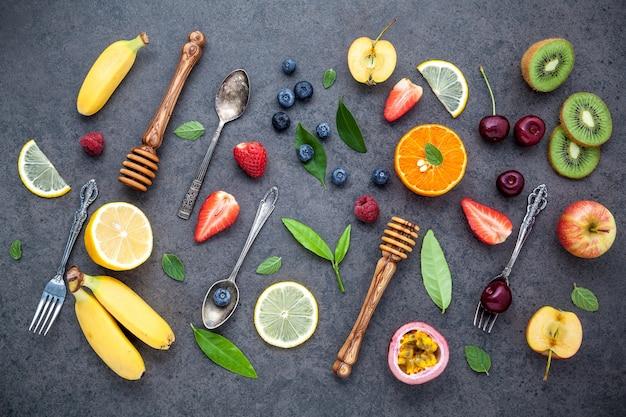 Flat lay various fresh fruits setup on dark stone background . summer and sweet menu concept.