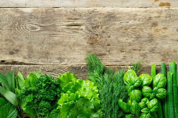 Flat lay of various fresh herbs on old wooden background. space for text