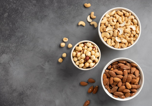 Flat lay of various types of nuts in white bowls on a gray wall. food border.