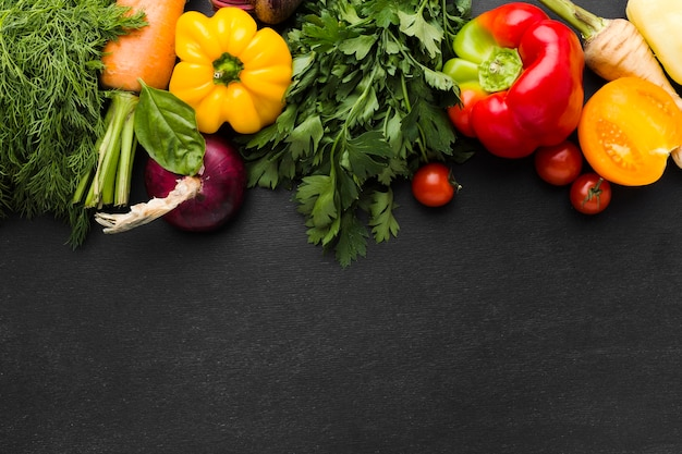 Плоская композиция из овощей на темном фоне с копией пространства