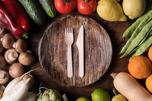 Плоская композиция из овощей с тарелкой