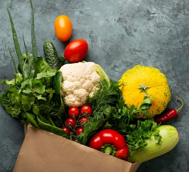Плоские лежат овощи на фоне штукатурки
