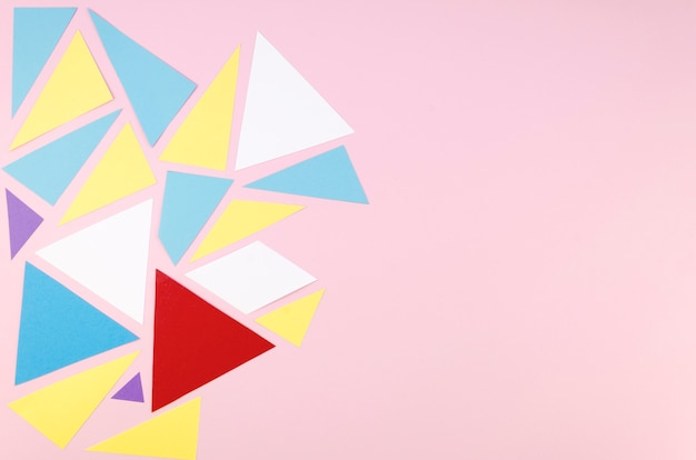 Flat lay of vibrant geometric paper triangles with copy space