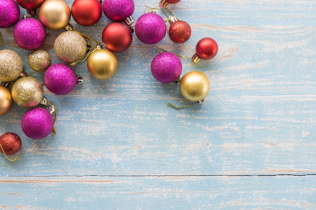 Flat lay view of colorful gold red pink purple christmas ornament ball on light blue wood