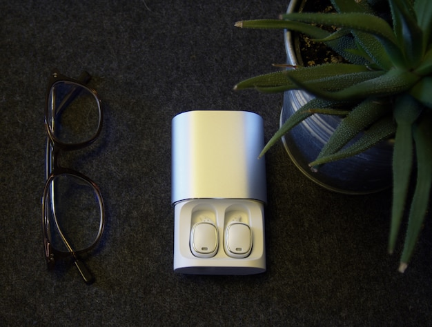 Flat lay view on white wireless headphones in charging case.