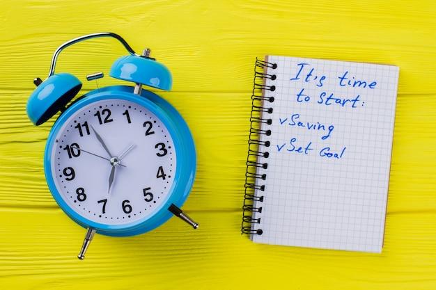 Плоский старинный будильник и блокнот со списком целей. пора начинать. желтый деревянный фон.