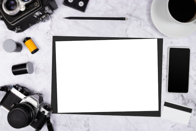 Flat lay vintage camera on white marble background with white blank paper copyspace