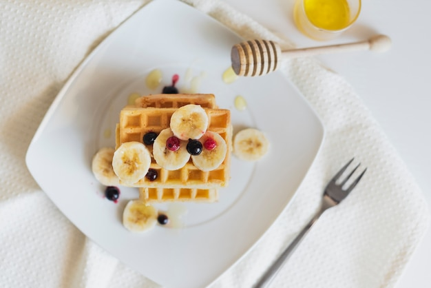 Flat lay of waffers with fruits and honey