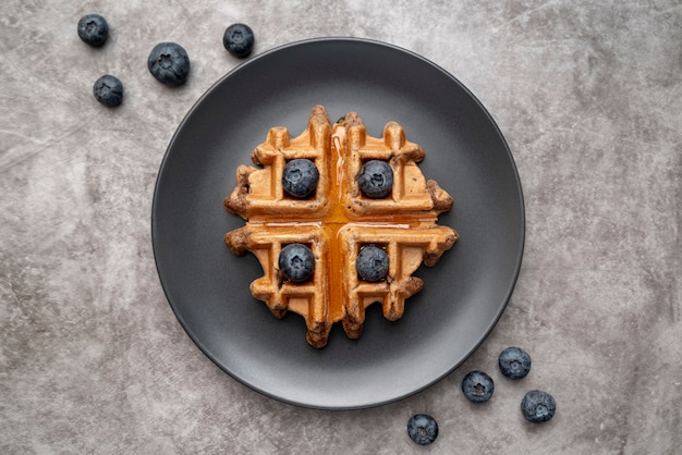 Flat lay of waffle on plate with blueberries