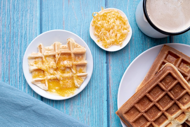 Flat lay of waffles on plate with melted cheese and beverage