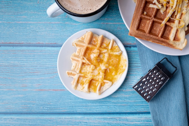 Flat lay of waffles on plated with grated cheese and beverage