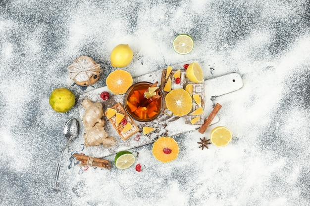 Cialde piatte e wafer di riso sul tagliere bianco con tisane, agrumi, cannella e colino da tè su superficie di marmo grigio scuro. orizzontale