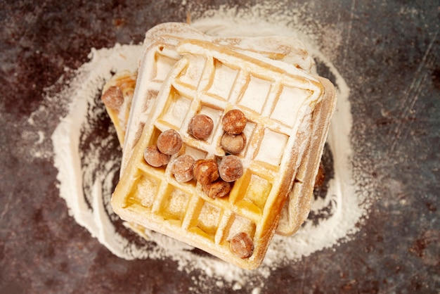 Flat lay of waffles with hazelnuts and powdered sugar