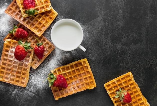 Lay piatto di cialde con latte e fragole