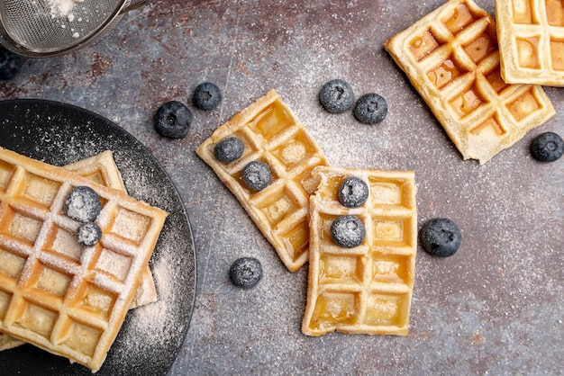 Flat lay of waffles with powdered sugar on top and blueberries