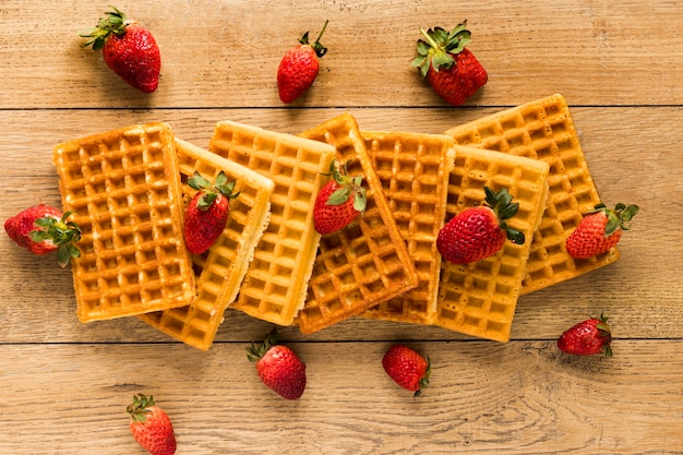 Flat lay of waffles with strawberries on wooden surface