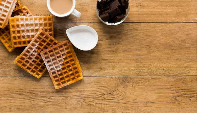 Flat lay of waffles on wooden surface with copy space