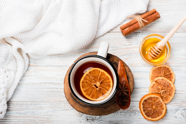 Flat lay of warm tea with orange