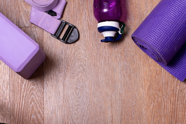 フラットレイウォーターボトル、マット、ブロック、ヨガ用ストラップ、木製の背景にフィットネス。健康的なライフスタイル、スポーツ、ダイエットのコンセプト。セレクティブフォーカス