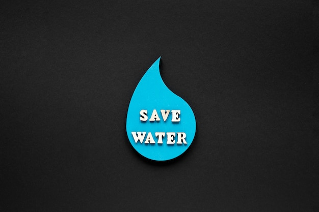 Flat lay of water drop with message