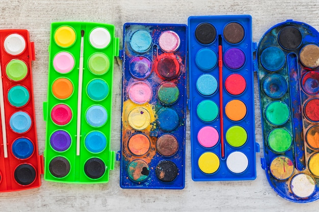 Flat lay watercolor paint in colored containers