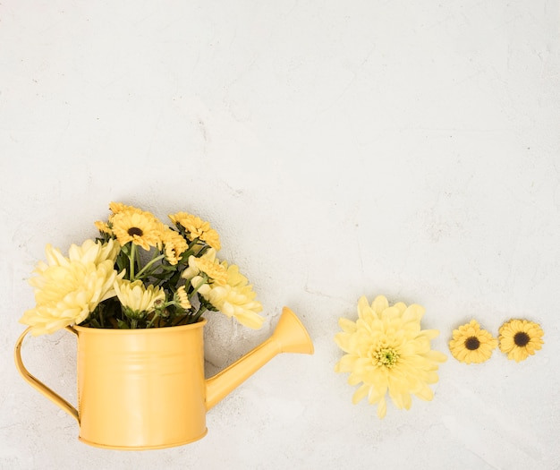 Flat lay watering can with yellow flowers