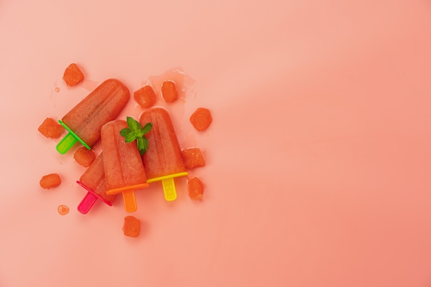 Flat lay watermelon ice cream pop stick by homemade on modern rustic pink paper wallpaper.
