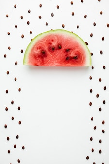 Flat lay watermelon umbrella with seeds on white background