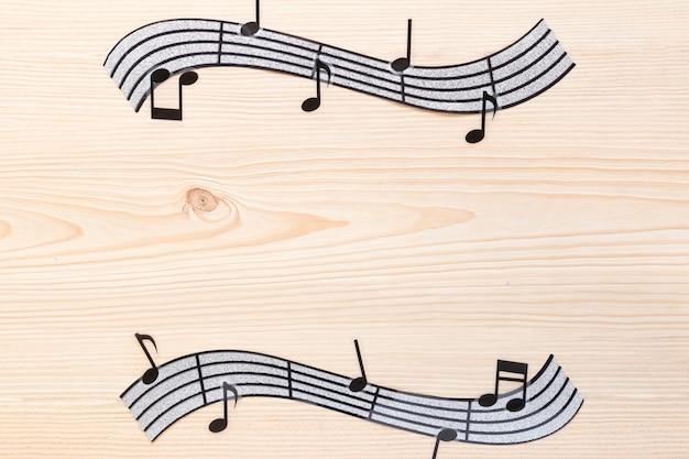 Плоские лежали волнистые музыкальные ноты с деревянным фоном