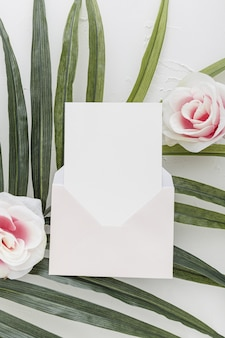 Flat lay of wedding invitation with roses