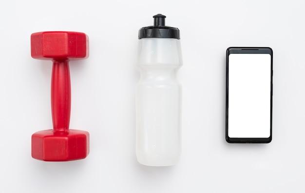 Lay piatto di peso con bottiglia d'acqua e smartphone