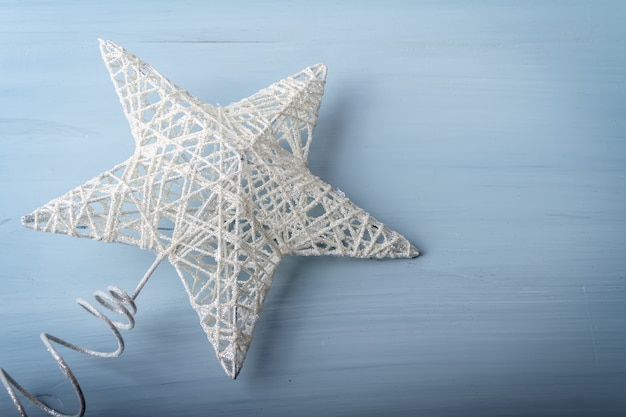 Flat lay of white christmas toy in the form of a star on wooden background