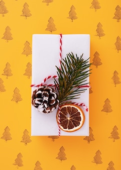 Flat lay of a white decorated gift box, christmas trees pattern in the orange background