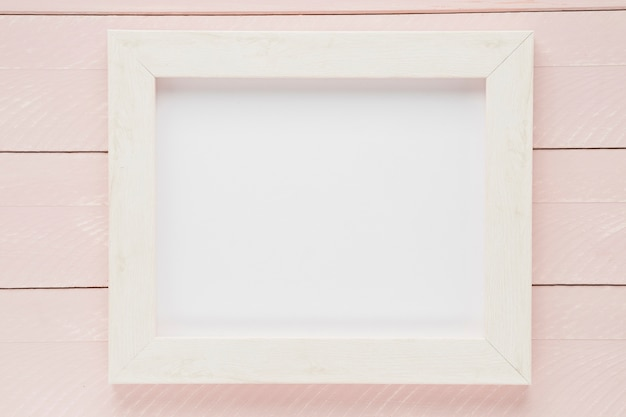 Flat lay white empty frame with wooden background