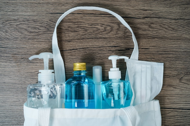 Flat lay of white fabric tote bag with face mask ,sanitizer hand gel and spray to protect from coronavirus or covid-19.